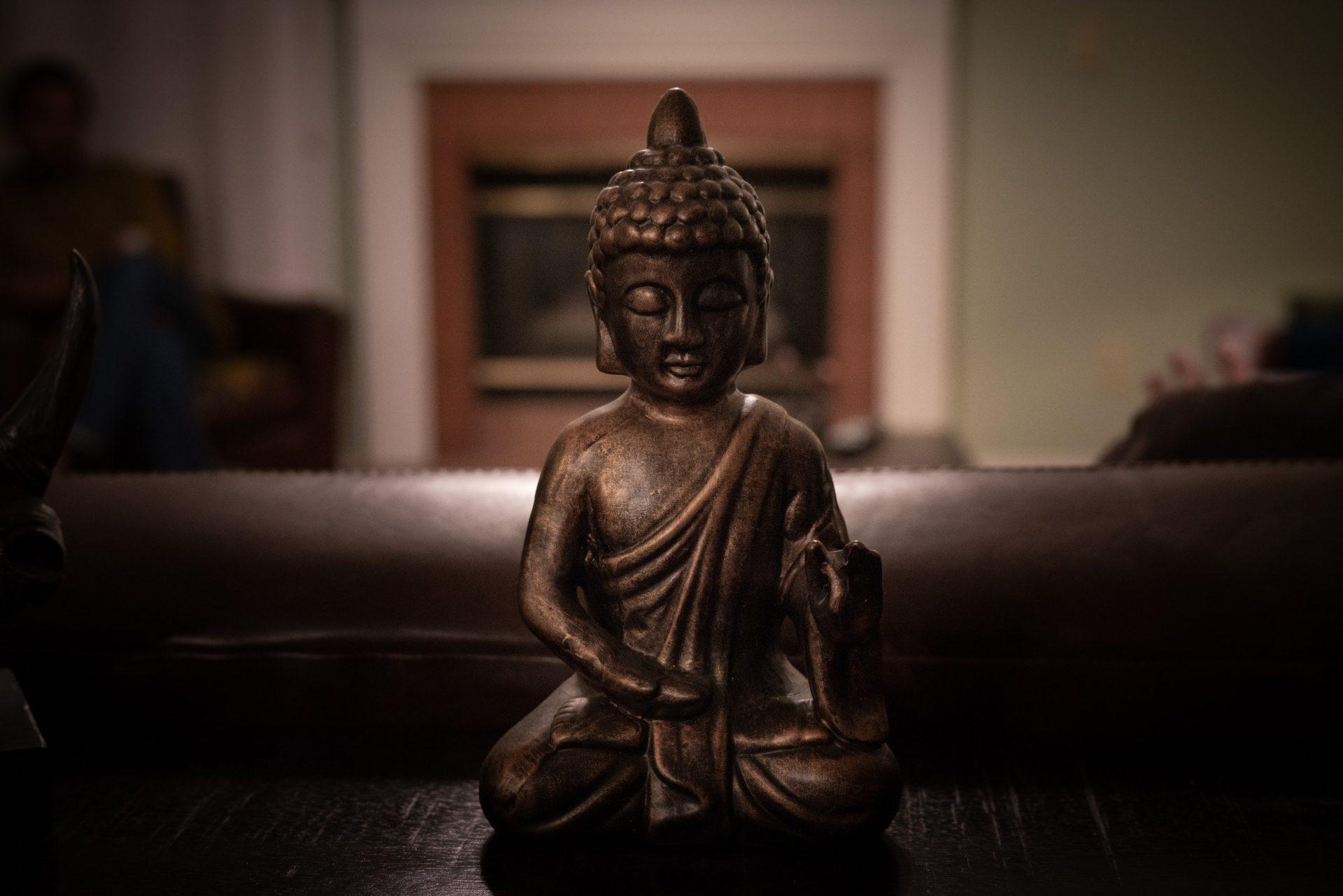 brass buddha figurine on black surface 1585716
